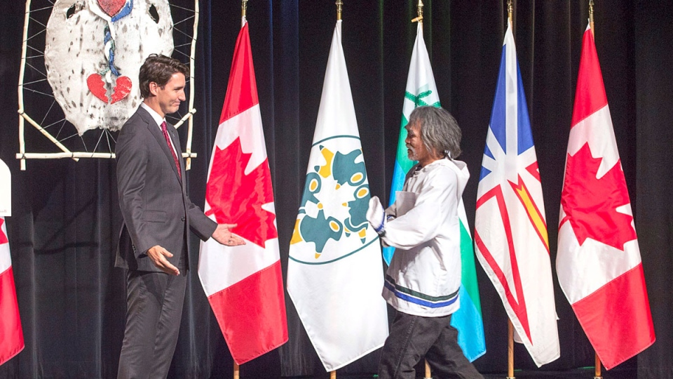 Prime Minister Justin Trudeau welcomes residential survivor Toby Obed to the stage after delivering an apology on behalf of the Government of Canada to former students of the Newfoundland and Labrador Residential Schools in Happy Valley-Goose Bay, N.L. on Friday, Nov. 24, 2017. The Canadian Press/Andrew Vaughan