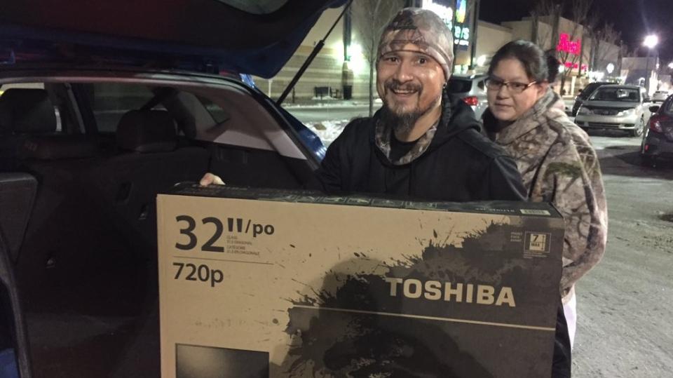 Garnett Crivea holds up his brand new TV purchased at Preston Crossing Best Buy in Saskatoon on Black Friday. (Mark Villani/ CTV News Saskatoon)