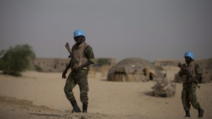 United Nations peacekeepers from Burkina Faso walk through a neighborhood on the outskirts of Timbuktu, Mali, during a patrol, Tuesday, July 23, 2013. (Rebecca Blackwell/AP Photo)