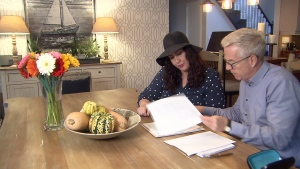 Jessica Hoffman shows Ross McLaughlin the paperwork that shows she had been paying double car payments for her old and new vehicle. (CTV)