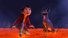 "This image released by Disney-Pixar shows characters Miguel, voiced by Anthony Gonzalez, left, and Dante in a scene from the animated film, ""Coco."" (Disney-Pixar via AP)"
