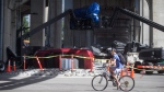 """A cyclist rides past a film set for the movie """"Deadpool 2"""" in Vancouver, B.C., on Tuesday August 15, 2017. (Darryl Dyck/THE CANADIAN PRESS)"""