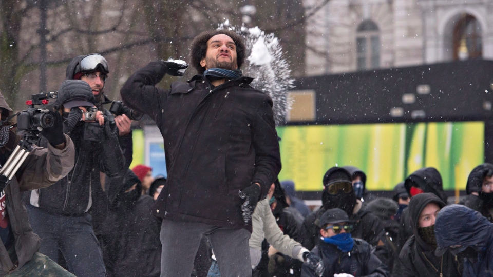 An antifacist demonstrator throws a snowball toward extreme right demonstrators in Quebec City on Saturday, November 25, 2017. (THE CANADIAN PRESS/Jacques Boissinot)