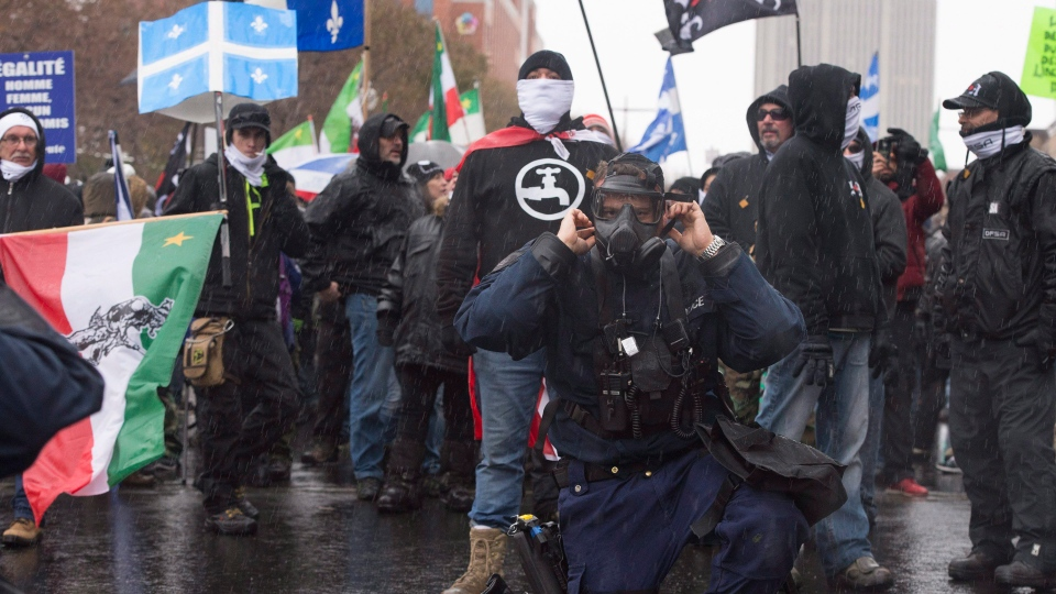 A Quebec police officer puts on his gas mask while standing in front of right wing group, Storm Alliance, during a demonstration where antifacists and extreme right group faced one another, in Quebec City on Saturday, November 25, 2017. (THE CANADIAN PRESS/Jacques Boissinot)