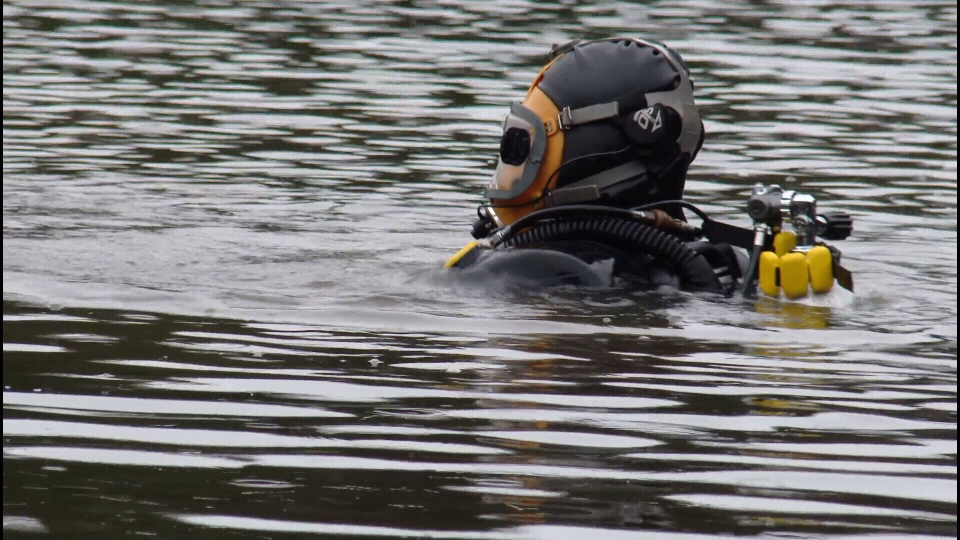 An RCMP diver searches Alpha Lake after a personal item belonging to missing woman Alison Leanne Raspa was found near the lake.