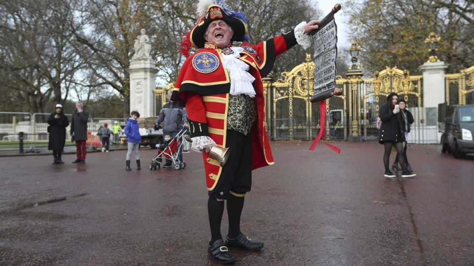Town Crier Tony Appleton shouts as he holds a scroll outside Green Park in central London near Buckingham Palace after it was announced that Prince Harry and Meghan Markle to be engaged. (Jonathan Brady/PA via AP)