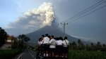 School students stand on a truck as their transport to go to school with the Mount Agung volcano spews smoke and ash in Karangasem, Bali, Indonesia, Tuesday, Nov. 28, 2017. Indonesia authorities raised the alert for the rumbling volcano to highest level on Monday and closed the international airport on the tourist island of Bali stranding some thousands of travellers.(AP Photo/Firdia Lisnawati)