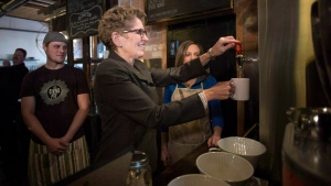 Ontario Premier Kathleen Wynne makes herself a cup of tea at a Toronto coffee shop, before making an announcement regarding the minimum wage in the province, on Thursday, Jan. 30, 2014. (THE CANADIAN PRESS/Chris Young)