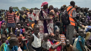 FILE - In this Saturday, June 17, 2017 file photo, men, women and children line up to be registered with the World Food Programme (WFP) for food distribution in Old Fangak, in Jonglei state, South Sudan. (AP Photo/Sam Mednick)