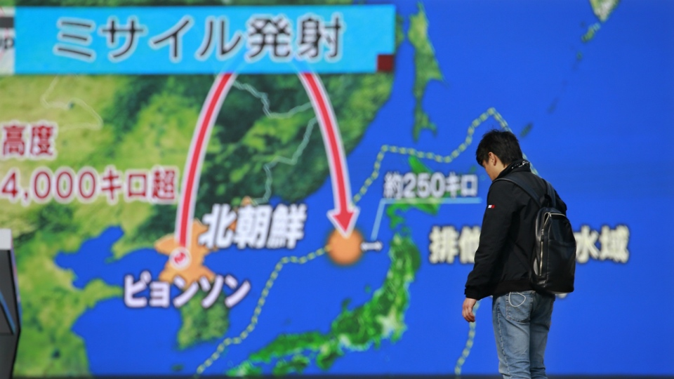 A man stands in front of a huge screen showing TV news program reporting North Korea's missile launch, in Tokyo on Wednesday, Nov. 29, 2017. (AP Photo/Shizuo Kambayashi)