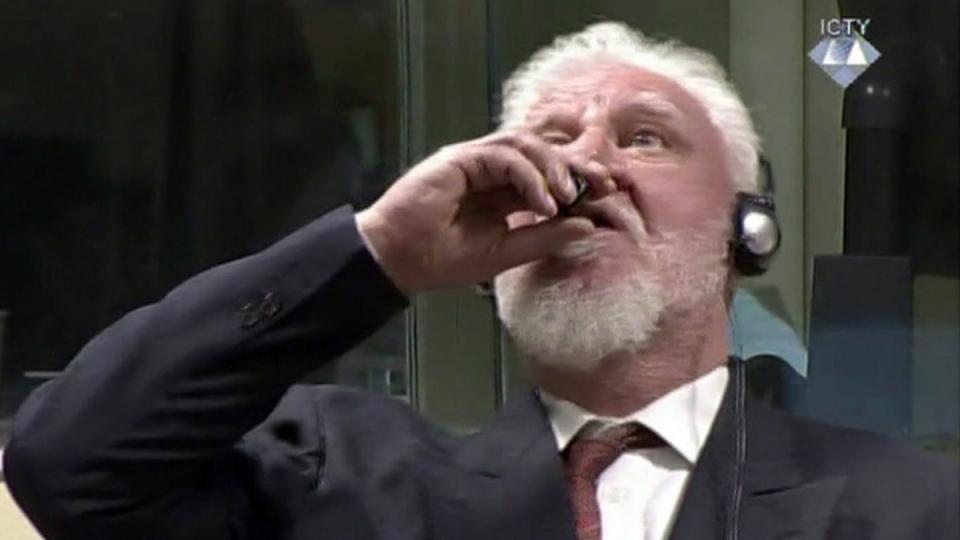 Slobodan Praljak brings a bottle to his lips, during a Yugoslav War Crimes Tribunal in The Hague, Netherlands, on Nov. 29, 2017. (ICTY via AP)