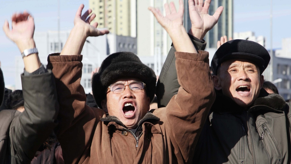 People cheer as they watch the news broadcast announcing North Korean leader Kim Jong Un's order to test-fire the newly developed inter-continental ballistic missile Hwasong-15, on Nov. 29, 2017. (Jon Chol Jin / AP)