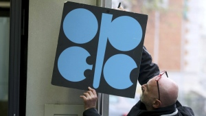 A worker attaches a poster of the Organization of the Petroleum Exporting Countries, OPEC, at their headquarters in Vienna, Austria, on Nov. 29, 2017. (Ronald Zak / AP)