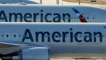 In this Monday, Nov. 6, 2017, file photo, a pair of American Airlines jets are parked on the airport apron at Miami International Airport in Miami. (Wilfredo Lee/AP Photo)