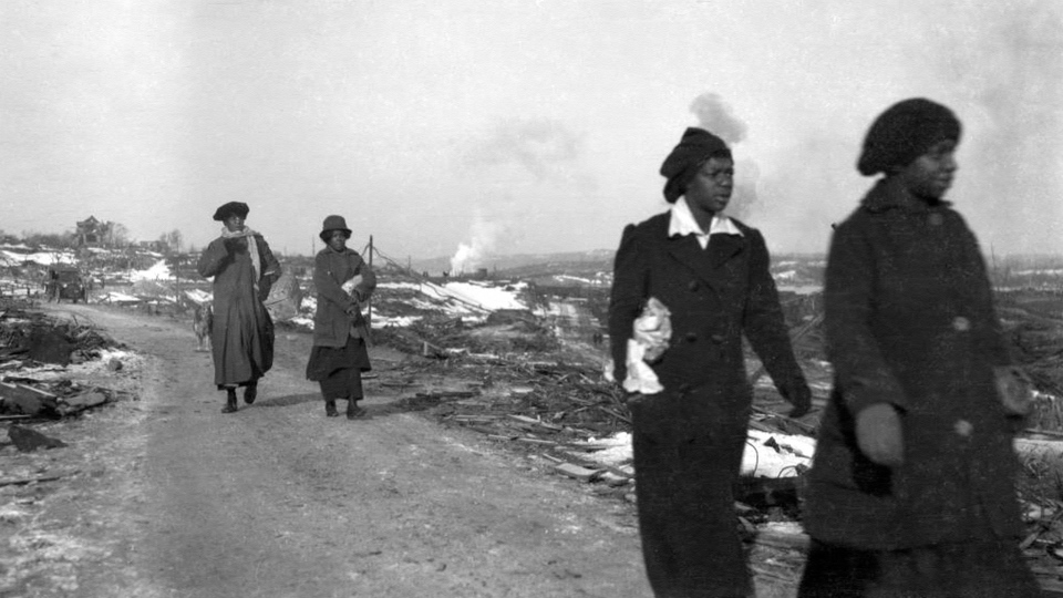 Women from Africville, the black district of Halifax, make their way through the rubble. (City of Toronto Archives)