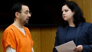 Former sports doctor Larry Nassar, left, stands with his attorney Shannon Smith as he pleads guilty to three counts of first-degree criminal sexual conduct in Judge Janice Cunningham's courtroom in Eaton County, Mich. on Wednesday, Nov. 29, 2017. (Matthew Dae /Lansing State Journal via AP)