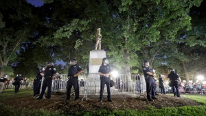 Police surround a Confederate monument during a protest to remove the statue at the University of North Carolina in Chapel Hill, N.C., on Aug. 22, 2017. (AP Photo/Gerry Broome)