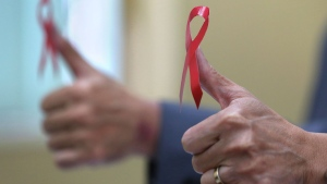 Philippine health officials pose with a red ribbon, the symbol of support and awareness for those living with HIV, on their thumbs to mark World Aids Day on Friday, Dec. 1, 2017 in Manila, Philippines. (AP Photo/Aaron Favila)