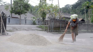 A woman sweeps a yard covered in volcanic ash from the eruption of Mount Agung in Karangasem, Bali, Indonesia, Friday, Dec. 1, 2017. Authorities have told tens of thousands of people to leave an area extending 10 kilometers (6 miles) from the volcano as it belches volcanic materials into the air. Mount Agung's last major eruption in 1963 killed about 1,100 people. (AP Photo / Firdia Lisnawati)