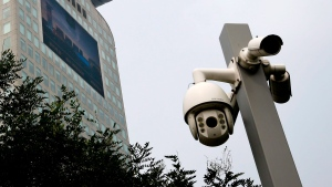 Surveillance cameras stand near the Pangu Plaza with a huge screen advertising his dragon-shaped design which owned by the exiled Chinese businessman Guo Wengui in Beijing, Thursday, Aug. 31, 2017. (AP Photo/Andy Wong)