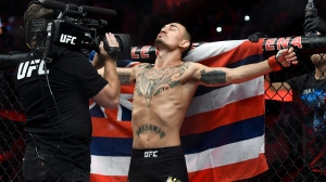 Max Holloway stands in front of the state flag of Hawaii as he prepares to fight Jose Aldo of Brazil during a UFC 218 featherweight mixed martial arts bout, Sunday, Dec. 3, 2017, in Detroit. (AP / Jose Juarez)
