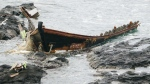 A wooden boat is left after being washed ashore in Tsuruoka, Yamagata prefecture, northern Japan Monday, Dec. 4, 2017. (Kyodo News)