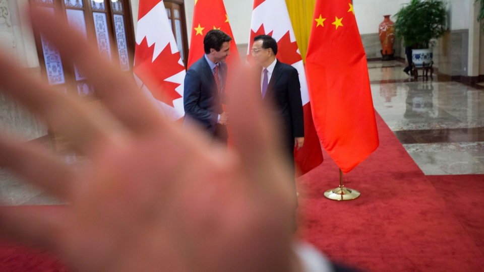 A security guard attempts to block a photographer as a picture is taken of Prime Minister Justin Trudeau being greeted by Chinese Premier Li Keqiang at the Great Hall of the People in Beijing, China on Monday, Dec. 4, 2017. THE CANADIAN PRESS/Sean Kilpatrick