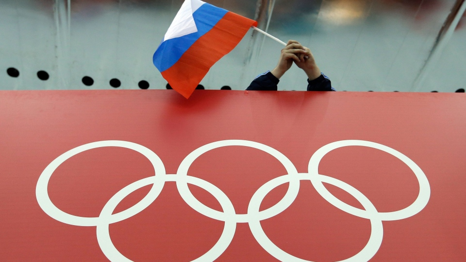 In this file photo, a Russian skating fan holds the country's national flag over the Olympic rings at Adler Arena Skating Center during the 2014 Winter Olympics in Sochi, Russia. (AP Photo/David J. Phillip, File)