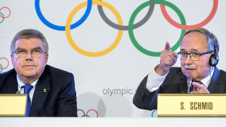 International Olympic Committee, IOC, President Thomas Bach from Germany, left, and Samuel Schmid, President of the IOC Inquiry Commission and former President of Switzerland, right, comment during a press conference after an Executive Board meeting, in Lausanne, Switzerland, Tuesday, Dec. 5, 2017. (Jean-Christophe Bott/Keystone via AP)