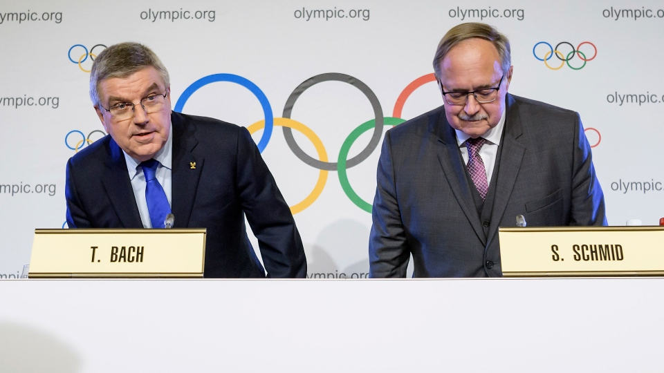 IOC President Thomas Bach from Germany, left, and Samuel Schmid, President of the IOC Inquiry Commission, right, take their seats as they arrive for a press conference in Lausanne, Switzerland, Tuesday, Dec. 5, 2017. (Jean-Christophe Bott/Keystone via AP)