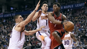 Phoenix Suns centre Alex Len and Devin Booker defend as Toronto Raptors guard Kyle Lowry looks for the pass during second half NBA basketball action in Toronto on Dec. 5, 2017. (Nathan Denette/THE CANADIAN PRESS)