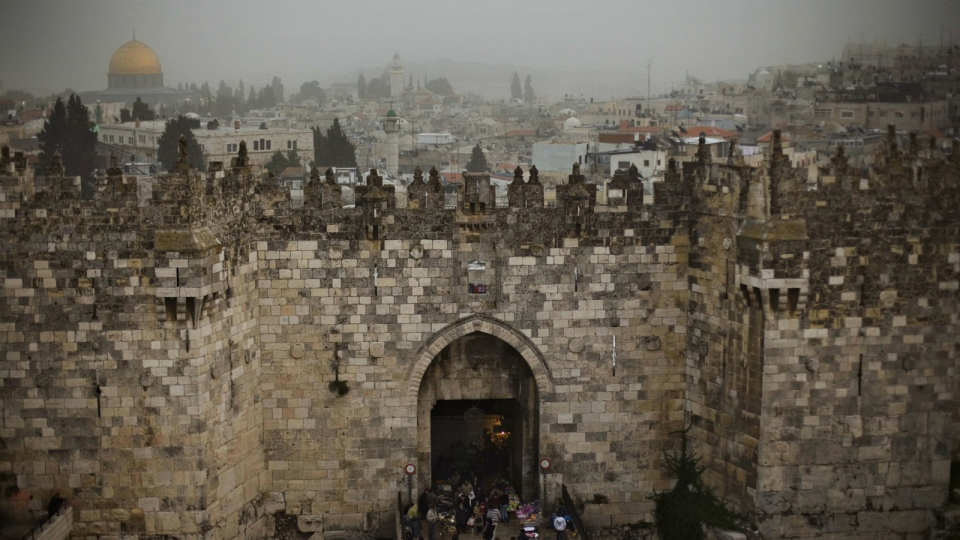 People walk in and out of the Damascus gate, while the Dome of the Rock, background and left, is seen on a cloudy, overcast day in Jerusalem's Old City on Feb. 19, 2009. (AP Photo/Bernat Armangue)