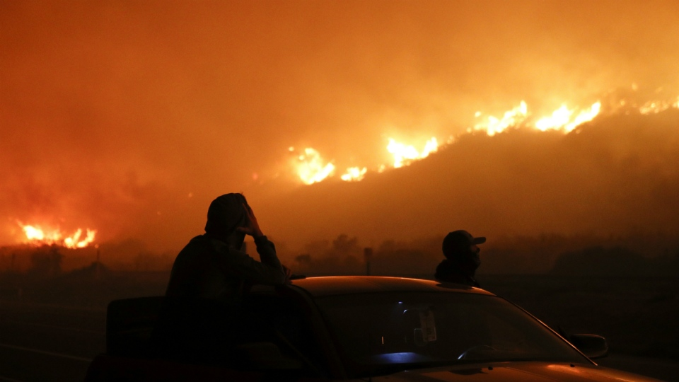 Two spectators watch as a wildfire burns along the 101 Freeway in Ventura, Calif. on Tuesday, Dec. 5, 2017. (AP Photo/Jae C. Hong)