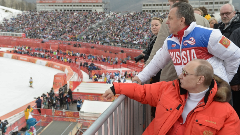 Russian President Vladimir Putin, foreground, watches downhill ski competition of the 2014 Winter Paralympics in Roza Khutor mountain district of Sochi, Russia, as Russia's sports minister Vitaly Mutko stands behind, on Saturday, March 8, 2014. (RIA-Novosti, Alexei Nikolsky, Presidential Press Service)