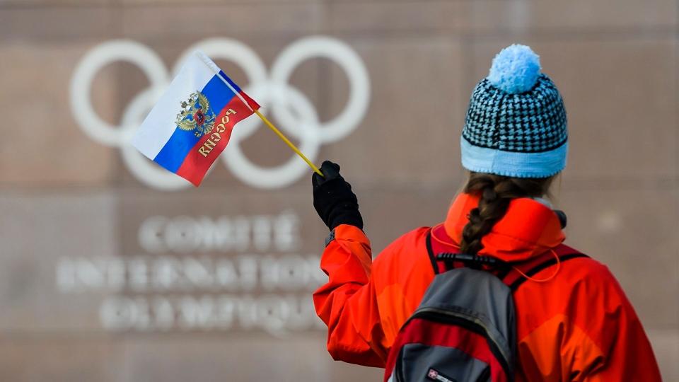 A woman waves a Russian flag outside of the International Olympic Committee (IOC) headquarters. (Jean-Christophe Bott, Keystone via AP)