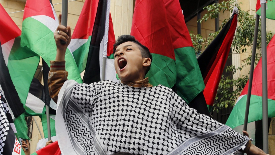 A child holds a Palestinian flag during a sit-in in the Bourj al-Barajneh Palestinian refugee camp, in Beirut, Lebanon, on Dec. 6, 2017. (Bilal Hussein / AP)