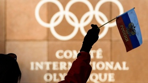 A woman waves a Russian flag outside of the International Olympic Committee (IOC) headquarters in front of the Olympic Rings prior to the opening of the first day of the executive board meeting of the International Olympic Committee (IOC) at the IOC headquarters, in Pully near Lausanne, on Tuesday, Dec. 5, 2017. (Jean-Christophe Bott, Keystone via AP)