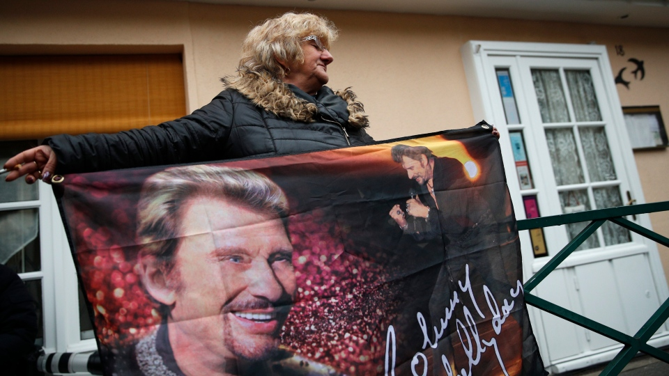 French fan Francoise Dordain displays a flag printed with images of Johnny Hallyday outside Hallyday's house in Marnes-la-Coquette, outside Paris, Wednesday, Dec.6, 2017. (AP Photo/Christophe Ena)