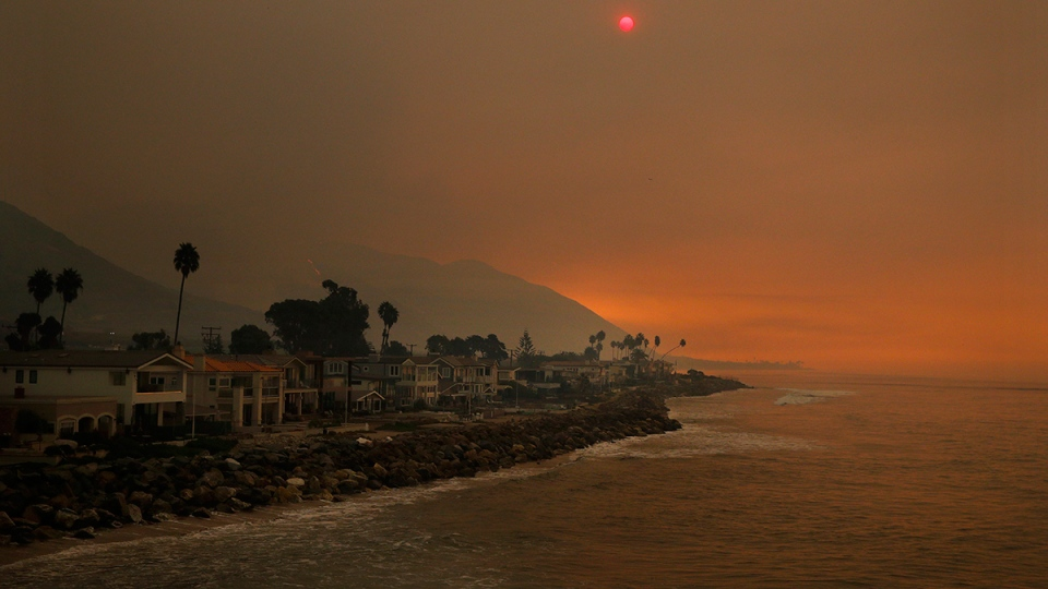 Homes stand along the beach as the sun is visible through thick smoke from a wildfire, Wednesday, Dec. 6, 2017, in Ventura, Calif. (AP / Jae C. Hong)