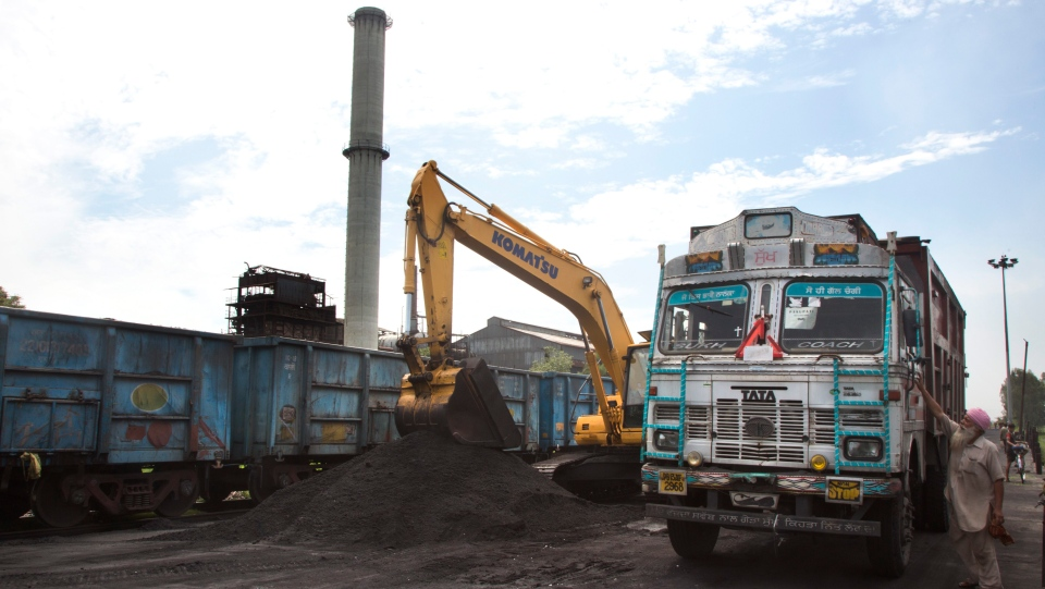 In this July 2017 file photo, domestically produced petroleum coke is loaded onto a truck to be transported to factories, at a railway station in Rampur, about 210 kilometers from New Delhi, India. (AP Photo/Vaishnavee Sharma, File)