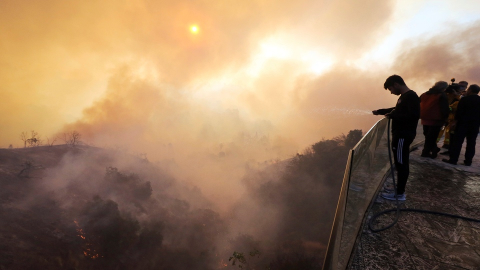 Aaron Kaboud sprays water off the deck of his family's home that was spared by a wildfire that hit the Bel Air district of Los Angeles on Wednesday, Dec. 6, 2017. (AP Photo/Reed Saxon)
