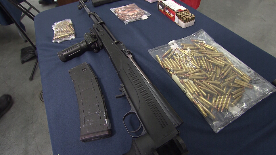 An assault rifle and ammunition are seen after police seized a large amount of weapons from a farmhouse in Langley, B.C. they believe was being used by gang members.