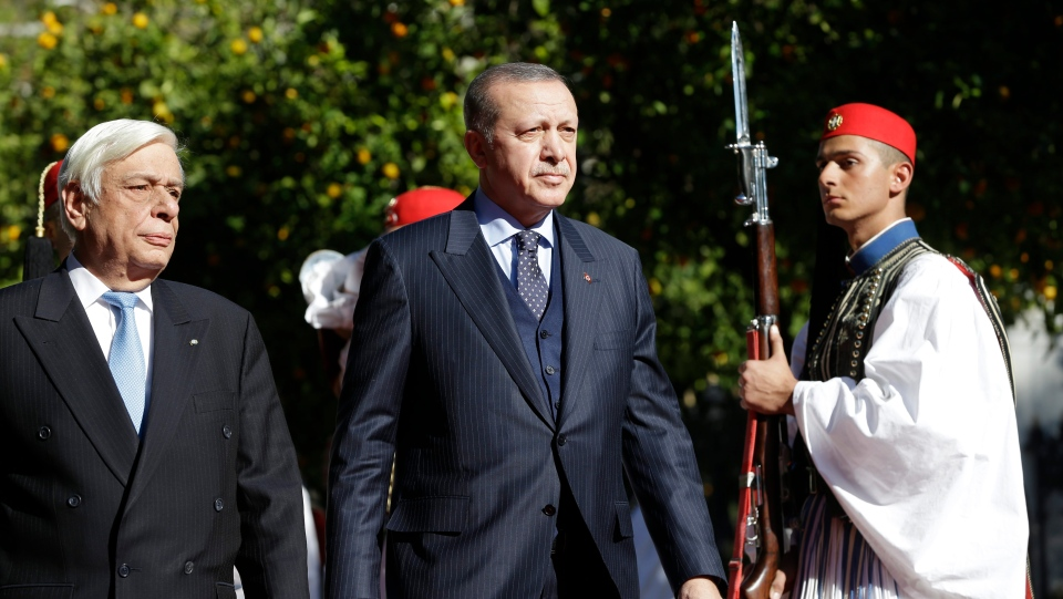 Greece's President Prokopis Pavlopoulos, left and Turkey's President Recep Tayyip Erdogan, centre, review the Presidential Guard during the welcome ceremony in Athens, Thursday, Dec. 7, 2017. (AP Photo/Thanassis Stavrakis)