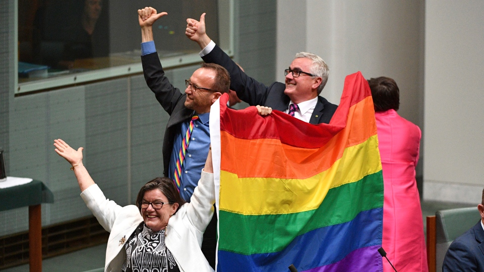 Members of parliament, from left, Cathy McGowan, Adam Brandt and Andrew Wilkie celebrate the passing of the Marriage Amendment Bill in the House of Representatives at Parliament House in Canberra, Thursday, Dec. 7, 2017. (Mick Tsikas/AAP Image via AP)