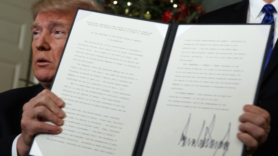 U.S. President Donald Trump holds up a proclamation to officially recognize Jerusalem as the capital of Israel, on Dec. 6, 2017. (Evan Vucci / AP)
