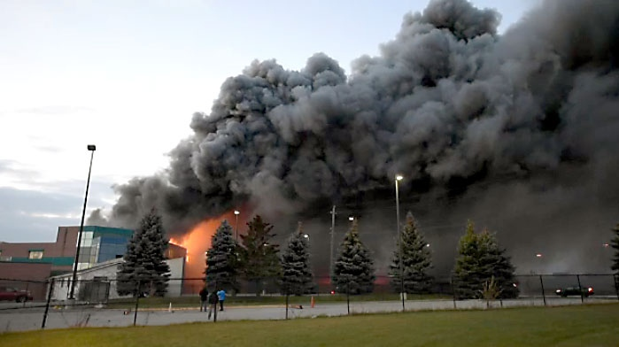 Huge plumes of black smoke billow from a food processing plant in Burlington on Dec. 6, 2017.