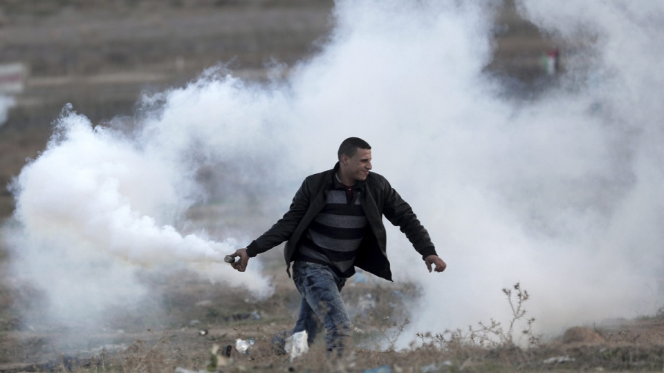 A Palestinian protester prepares to throw back a teargas canister during clashes on the Israeli border with Gaza, on Dec. 7, 2017. (Khalil Hamra / AP)