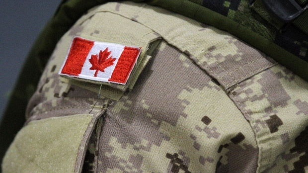 A Canadian flag sits on the shoulder of a Canadian Forces member leaving from CFB Trenton, in Trenton, Ont., on Thursday, Oct. 16, 2014. (The Canadian Press/Lars Hagberg)