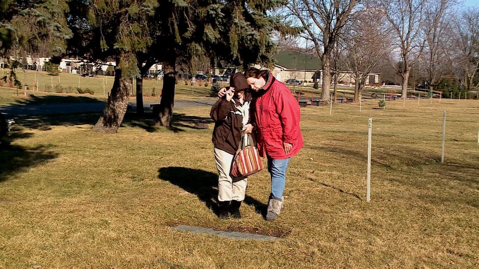 Valerie and Lucille Hannah stand at their family grave site at Capital Memorial Gardens in Ottawa, Ont. where several bronze vases went missing.
