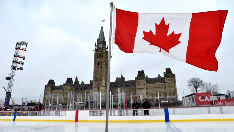 A Canadian flag standing on the ice flies in front of Centre Block before the official inauguration of the Canada 150 Rink on Parliament Hill in Ottawa on Thursday, Dec. 7, 2017. (THE CANADIAN PRESS / Justin Tang)
